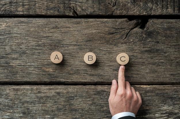Mano di un uomo d'affari che sceglie la lettera c su tre opzioni in un'immagine concettuale di pianificazione e visione aziendale.