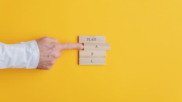Mano di un uomo d'affari che sceglie un piano un'opzione