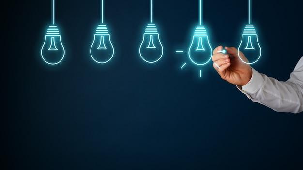 Mano di un uomo d'affari che disegna lampadine sull'interfaccia virtuale con penna stilo incandescente con una delle lampadine illuminate in un'immagine concettuale. su sfondo blu con copia spazio.