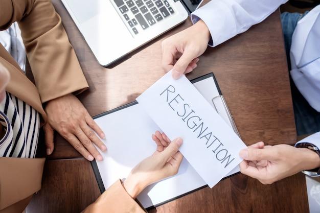 Mano di un uomo d'affari in mano una lettera di dimissioni su un tavolo di legno al suo capo