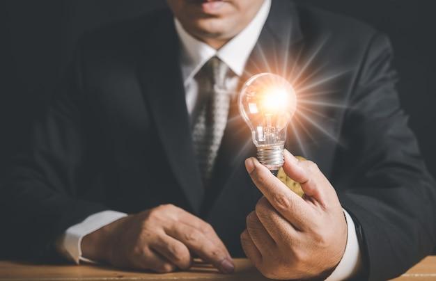 Mano dell'uomo d'affari che tiene la lampadina illuminata, idea, innovazione e concetto di ispirazione, copia dello spazio.