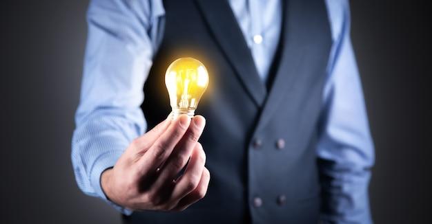 Mano dell'uomo d'affari che tiene la lampadina illuminata
