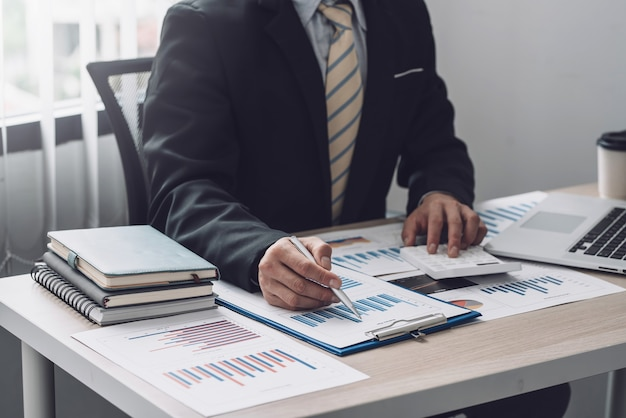 Mano di un uomo d'affari che tiene una penna che punta una calcolatrice grafica per calcolare le statistiche in ufficio.