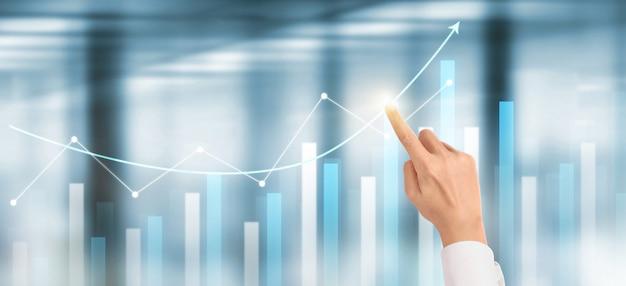 Crescita del grafico del piano dell'uomo d'affari della mano e aumento degli indicatori positivi del grafico nel suo affare