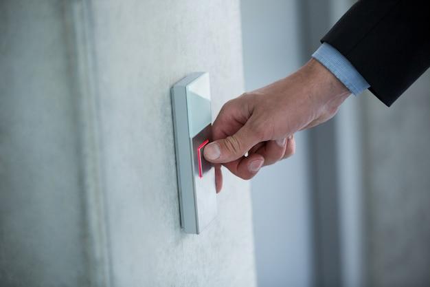 Mano di un uomo d'affari che preme il bottone in un elevatore