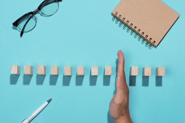 La mano dell'uomo d'affari ferma il domino continuamente rovesciato