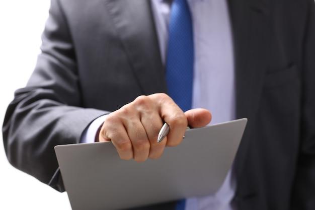 Mano dell'uomo d'affari in vestito che riempie e firma con il modulo di accordo di partenariato della penna d'argento ritagliato al primo piano del rilievo.