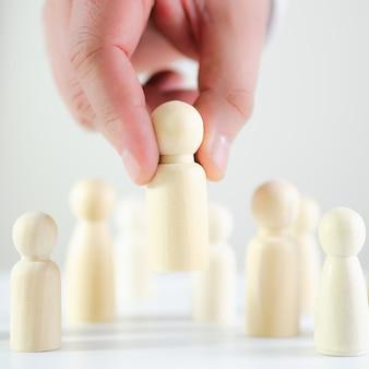 Mano di un uomo d'affari che prende una figura di legno di un uomo nell'immagine concettuale della ricerca, assumendo e licenziando i lavoratori, promozione
