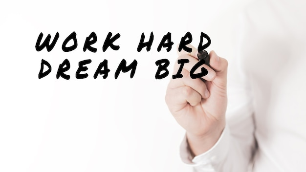 Mano di un uomo d'affari che scrive work hard dream big con pennarello nero
