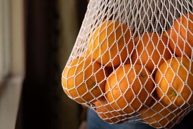 Portare a mano la busta di plastica riutilizzabile riutilizzabile. eco-friendly e sostenibilità arancione nella borsa a rete. stile di vita minimo per salvare la terra verde e l'ambiente. Foto Premium