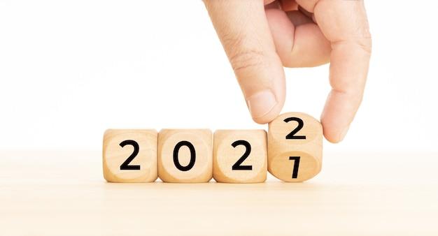 Blocchi di legno che cambiano a mano con il numero dal 2021 al 2022. concetto di capodanno. copia spazio.