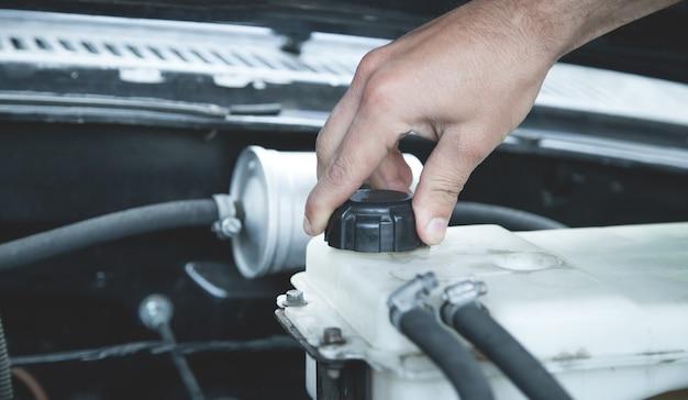 Mano che controlla il livello del liquido di raffreddamento del motore dell'auto.