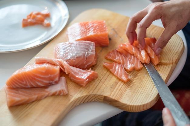 Chef a mano con salmone crudo affettato di coltello sul tagliere