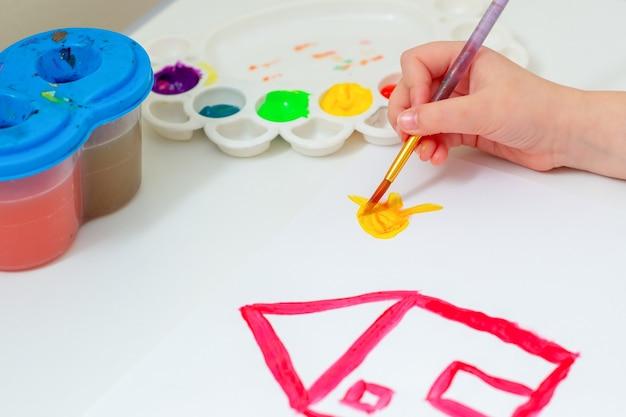 Mano del bambino che disegna sole giallo con casa rossa con pennello e acquerelli su foglio di carta bianco. concetto di opera d'arte.