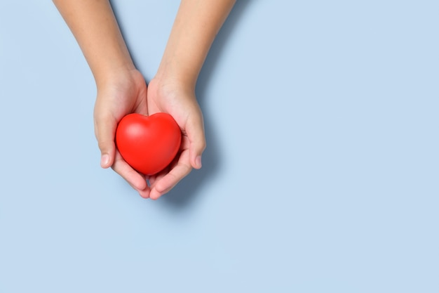 Mano bambino che tiene cuore rosso su sfondo blu, donazione, felice beneficenza volontaria, responsabilità sociale csr, giornata mondiale del cuore, giornata mondiale della salute, concetto di giornata mondiale della salute mentale