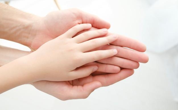 Mano di un bambino nelle mani della madre isolata su uno sfondo bianco