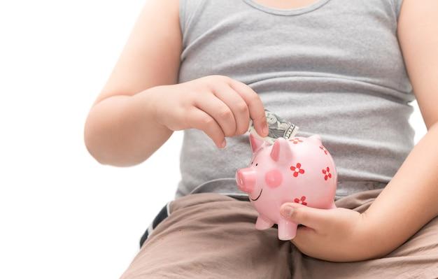 Il bambino della mano ha messo le banconote del dollaro nel porcellino salvadanaio isolato su fondo bianco, conservante il concetto dei soldi