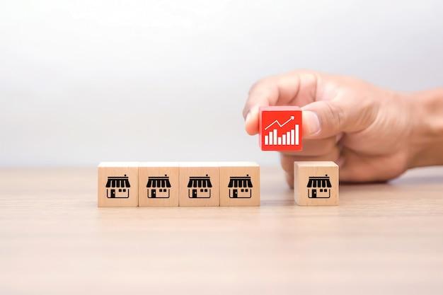 La mano sceglie un blog giocattolo di legno a forma di cubo con il simbolo del grafico commerciale e le icone di marketing in franchising.
