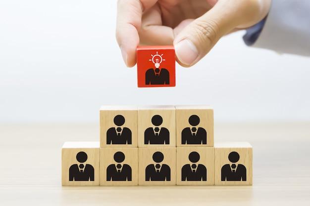 La mano sceglie l'icona dell'uomo d'affari sul blocco di legno.