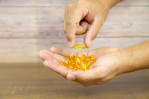 Mano scegliere una capsula di olio di fegato di merluzzo da una pila di olio di fegato di merluzzo o olio di pesce.