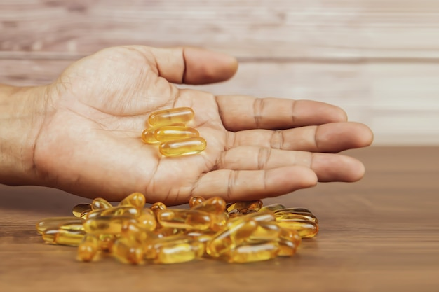 Scegli a mano una capsula di olio di fegato di merluzzo da una pila di olio di fegato di merluzzo o olio di pesce.