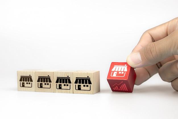 La mano sceglie i blog di legno del giocattolo del cubo con l'icona del negozio di vendita di franchising e l'icona del grafico.