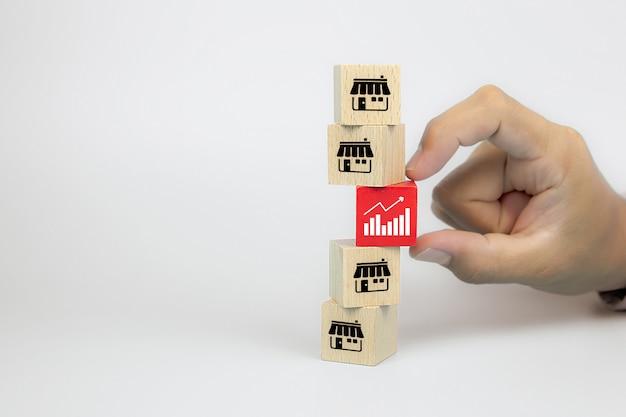 La mano sceglie l'icona del grafico con il deposito delle icone di vendita di franchising sul blog del giocattolo di legno del cubo è impilata per la crescita di affari e la strategia di espansione del ramo di finanziario.
