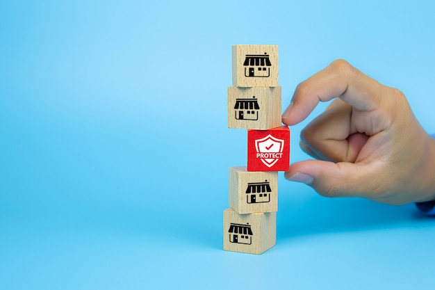 La mano sceglie l'icona dell'assicurazione con il deposito delle icone di vendita di franchising sul blog del giocattolo di legno del cubo è impilata. concetti gestione dei rischi e strutture finanziarie stabili.