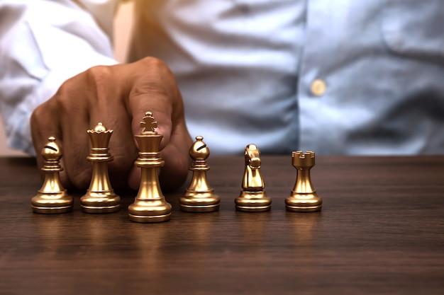 La mano sceglie il lavoro di squadra del supporto di scacchi del re sulla scacchiera.