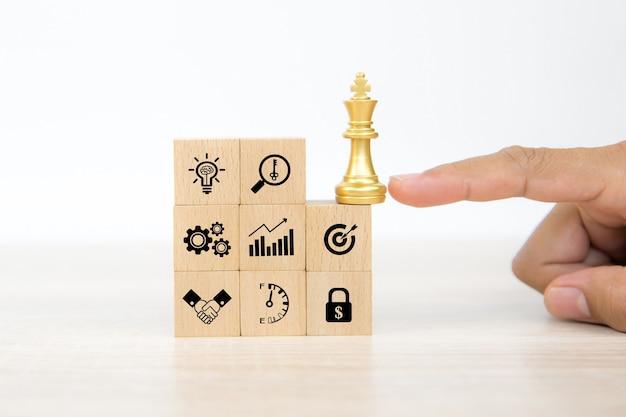 La mano sceglie il re degli scacchi su blocchi di legno impilati con l'icona di affari.