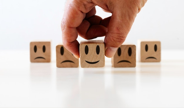 Mano sceglie la faccina sorridente e l'icona faccia triste sul cubo di legno soddisfazione, cliente, concetto di qualità