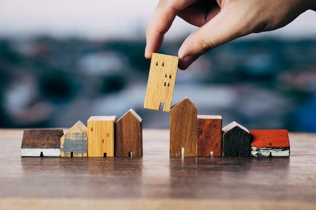 Mano che sceglie mini modello di casa in legno dal modello e fila di monete sul tavolo di legno