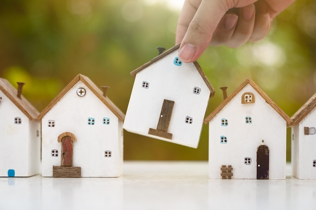 Mano che sceglie il modello di mini casa in legno dal modello