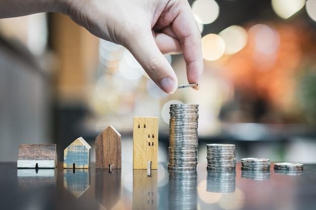 Mano che sceglie fila di moneta moneta sul tavolo in legno e mini casa in legno