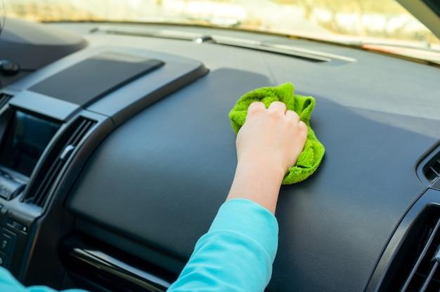 Pulire a mano l'interno dell'auto, pulizia dell'auto della console con un panno in microfibra. igiene e pulizia in un concetto di auto privata.