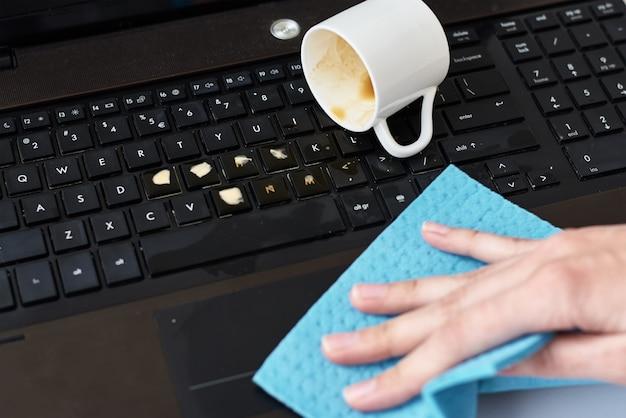 La mano pulisce il caffè versato sulla tastiera del laptop con uno straccio