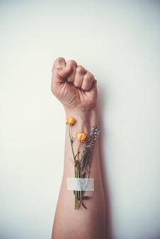 Mano serrata a pugno con fiori. problemi adolescenziali, malattie incurabili, relazioni sociali, il concetto