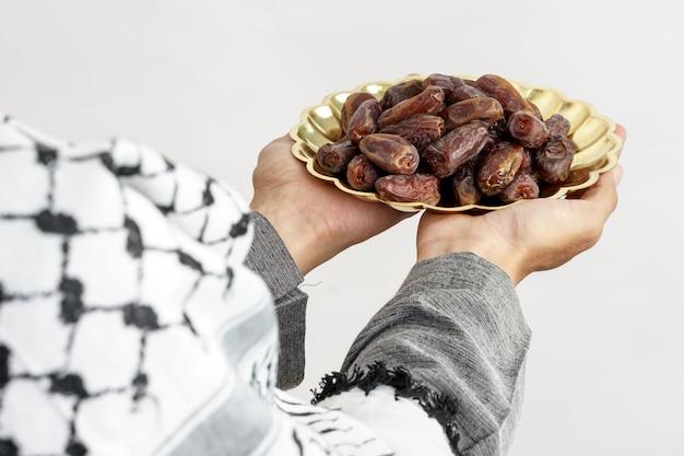 Frutta alta vicina delle date della tenuta della mano