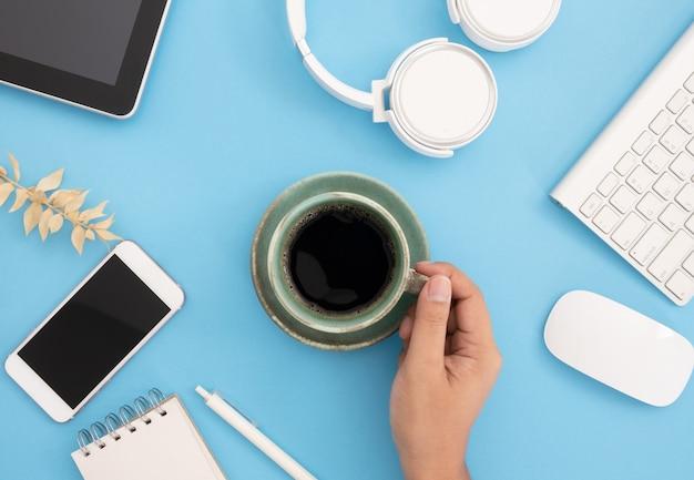 Tazza da caffè a mano, smartphone, cuffie, mouse e tastiera e altro su sfondo azzurro