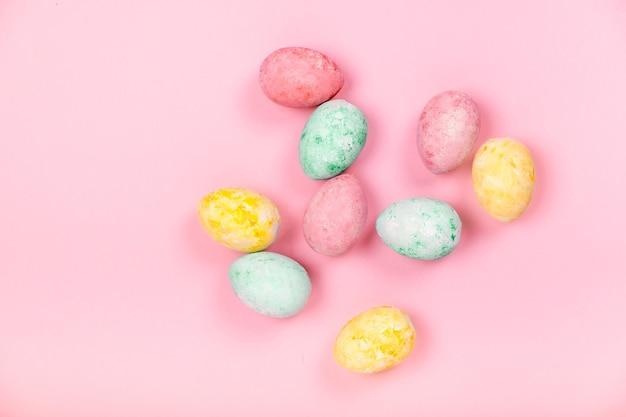 Uova di pasqua colorate a mano su fondo astratto rosa chiaro / copyspace vista orizzontale superiore. felice pasqua concetto