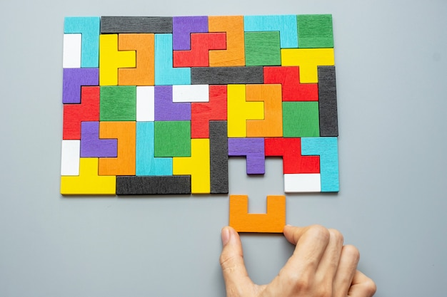 Mano che collega il blocco di forma geometrica con pezzi di puzzle in legno colorato.