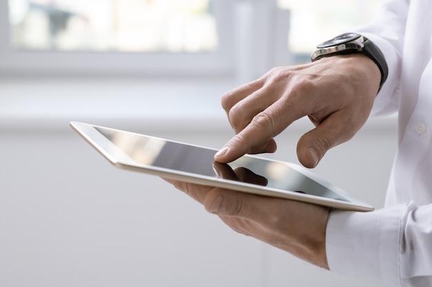 Mano dell'uomo d'affari contemporaneo con tablet che punta allo schermo durante la presentazione o lo scorrimento dei dati online