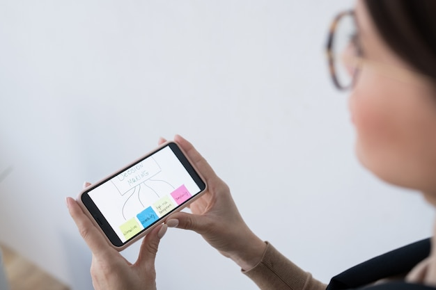 Mano della donna di affari contemporanea guardando attraverso il diagramma di flusso del processo decisionale sullo schermo dello smartphone