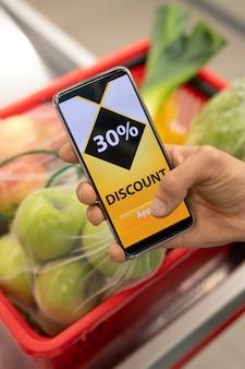 Mano di una donna matura contemporanea che tiene in mano uno smartphone e mostra un buono sconto online mentre si visita un supermercato