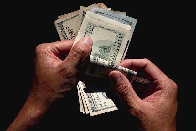 Mano che conta le banconote in dollari americani su sfondo nero