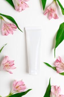 Mockup di tubo vuoto crema per le mani su sfondo bianco floreale.