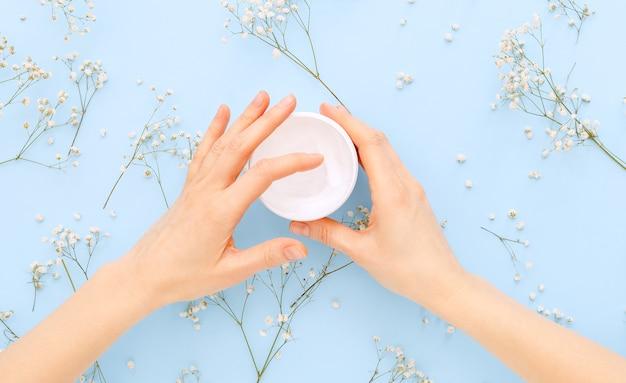 Crema per le mani, mani femminili che applicano cosmetici crema naturali organici su uno sfondo colorato blu pastello. crema per la cura della pelle in barattolo per mani, corpo.