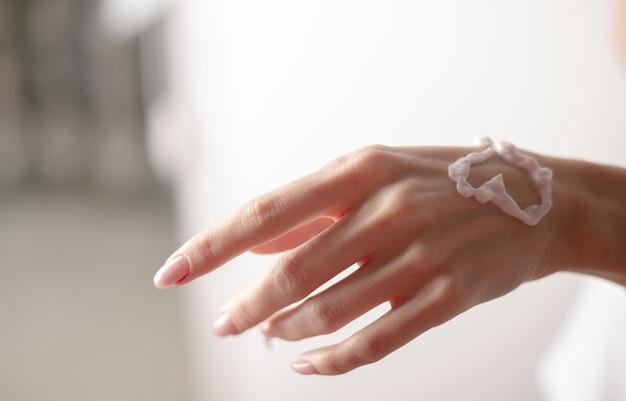 Crema per le mani sulla mano di una donna, a forma di cuore. giovane donna che applica crema per le mani