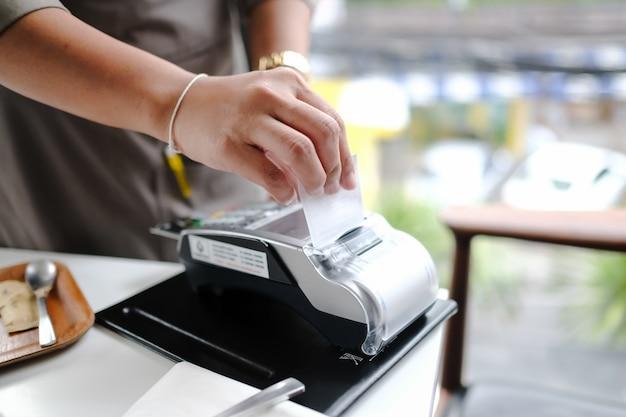 Mano del cliente che paga con carta di credito senza contatto con tecnologia nfc. barista con una macchina del lettore di carte di credito al bancone del bar con la carta di credito femminile della tenuta. concentrarsi sulle mani.