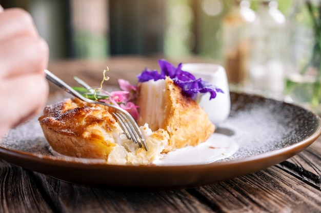 Una mano che taglia un pezzo di torta al cocco con una bella decorazione in un piatto da mangiare con la forchetta